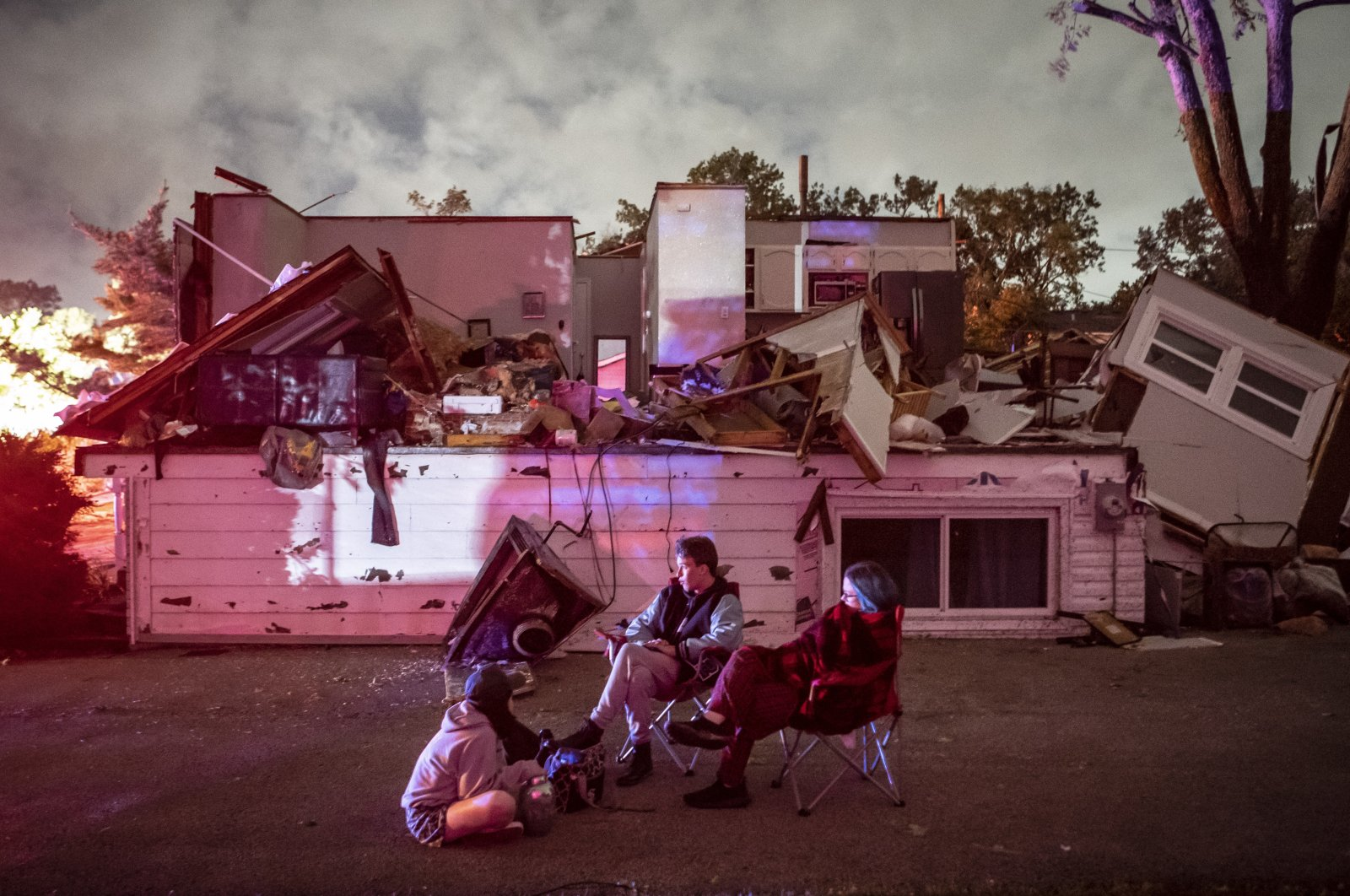 Bridget Casey sits in the driveway of her severely damaged home with her son Nate, 16, and daughter Marion, 14, after a tornado swept through the area in Woodridge, Ill., the U.S., June 21, 2021. (AP Photo)