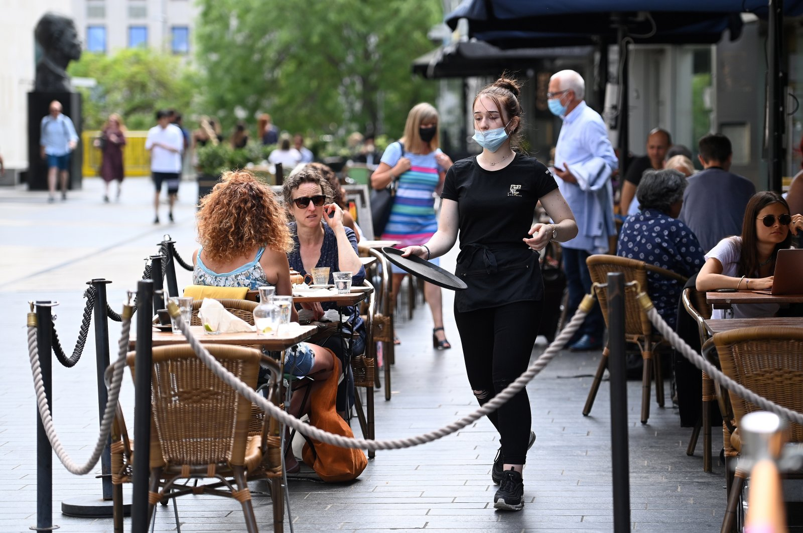 A busser moves to clean a table at a restaurant in London, Britain, June 15, 2021. (EPA Photo)