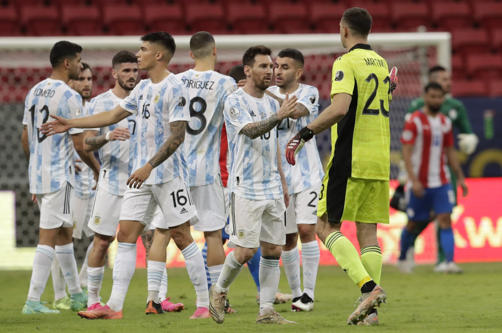 Argentina's players greet each other at the end of a Copa America match against Paraguay at the National Stadium in Brasilia, Brazil, June 21, 2021. (AP Photo)