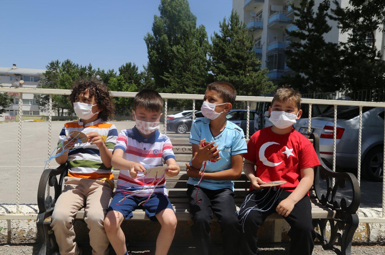 Children wearing protective masks sit on a bench, in Erzurum, eastern Turkey, June 21, 2021. (AA PHOTO)