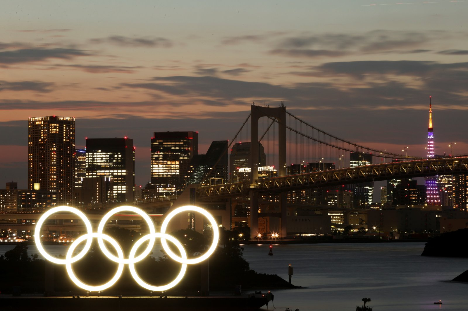 A long-exposure photo of the Olympic Rings on a floating platform with the Rainbow Bridge in the background ahead of the Tokyo 2020 Olympic Games, Tokyo, Japan June 21, 2021. (Reuters Photo)