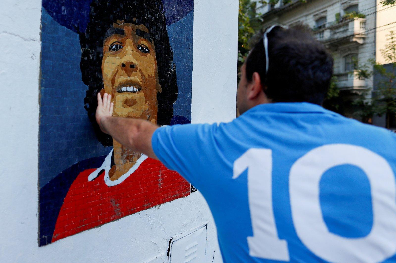 A man touches a mosaic made by the cultural organization Comando Maradona as a homage to late Argentine soccer superstar Diego Armado Maradona, Buenos Aires, Argentina, Feb. 25, 2021. (Reuters Photo)