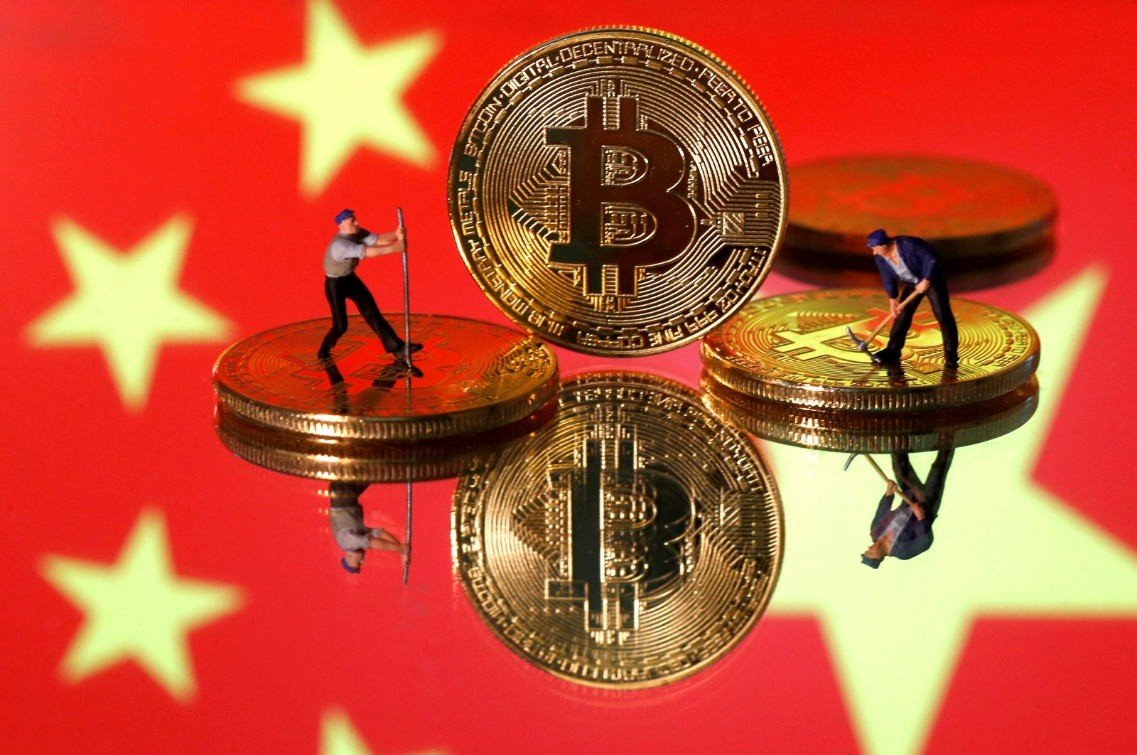 Small toy figurines are seen on representations of the Bitcoin virtual currency displayed in front of an image of China's flag in this illustration picture, April 9, 2019. (Reuters Photo)