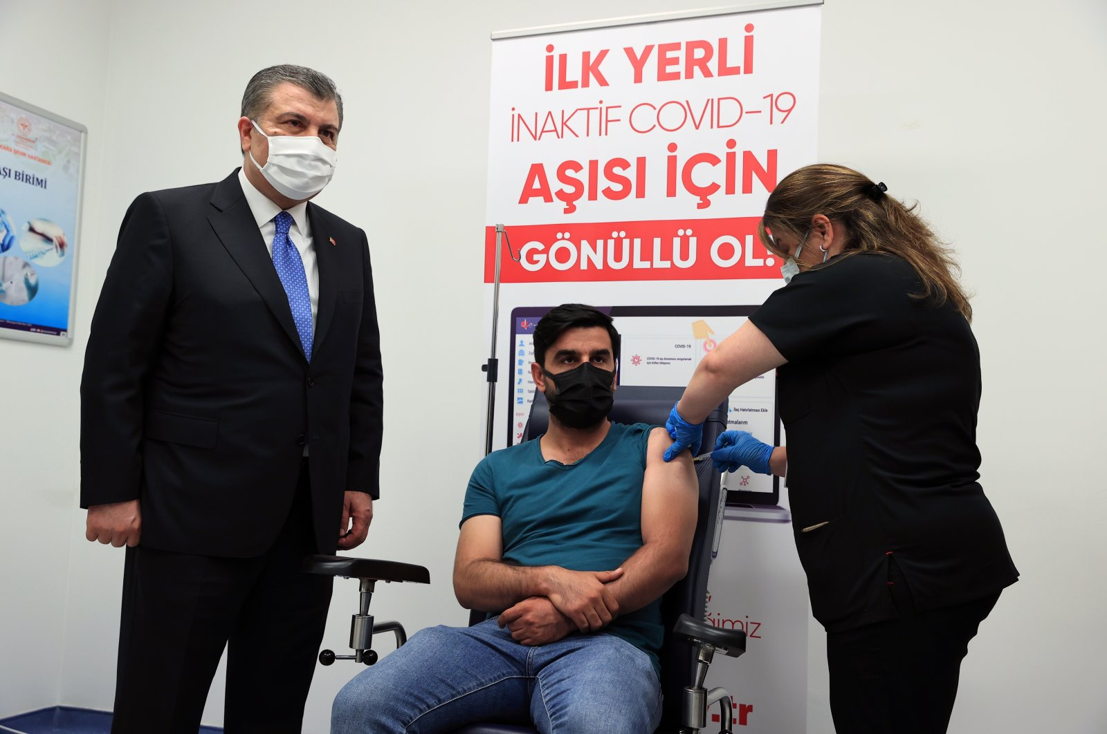 Yasin Kandemir, the first volunteer of the Phase 3 trial, gets vaccinated as Health Minister Fahrettin Koca looks on, in the capital Ankara, Turkey, June 22, 2021. (AA PHOTO)