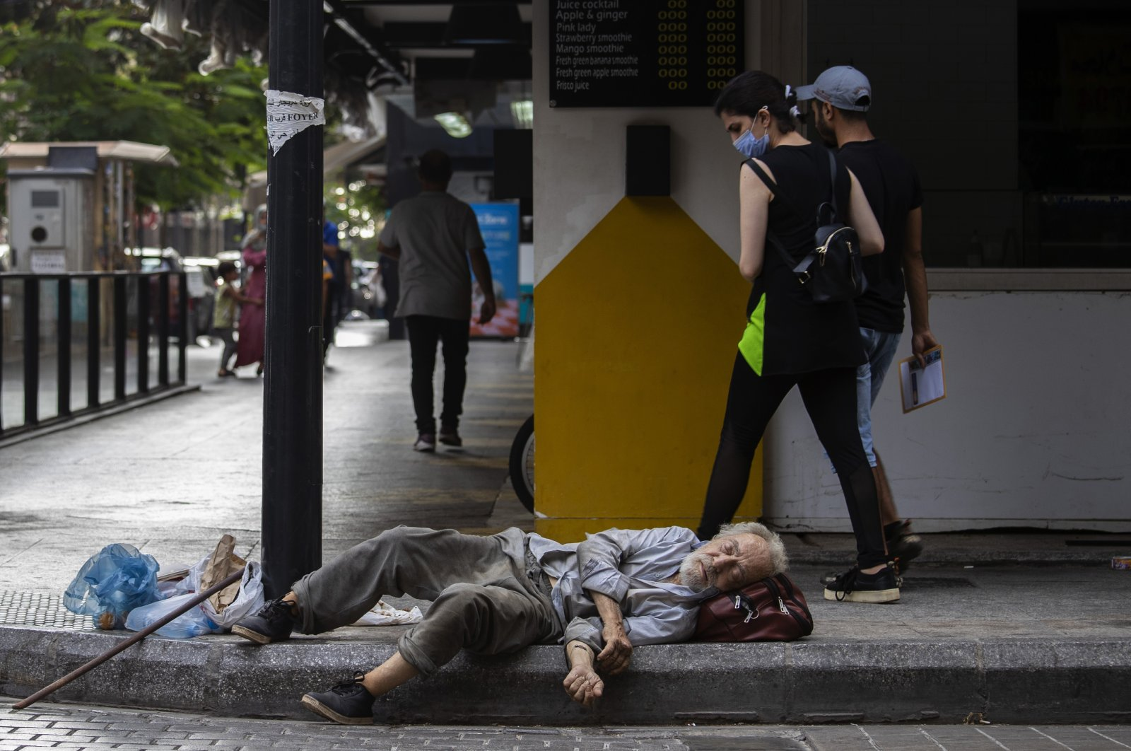 A woman looks at a homeless Lebanese man who sleeps on the ground at Hamra Street in Beirut, Lebanon, Friday, July 17, 2020. (AP Photo)