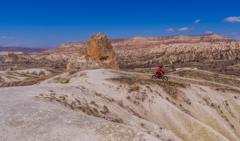 A rider on a dirt bike navigates rock formations near fairy chimneys in Cappadocia, Turkey, May 19, 2021. (Shutterstock Photo)