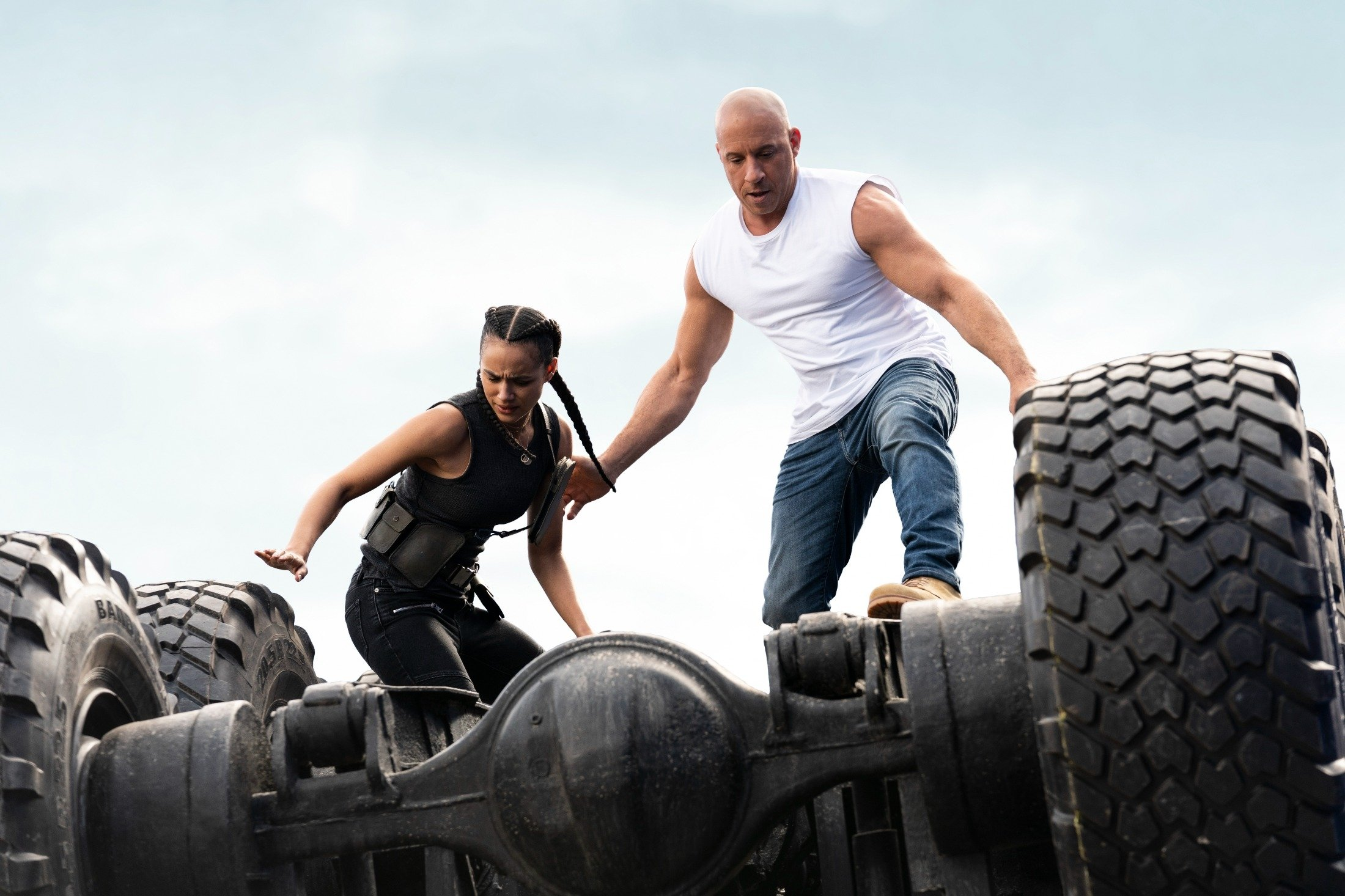Nathalie Emmanuel (L), and Vin Dieselprepare to jump off a vehicle, in a scene from the movie'F9: The Fast Saga.' (Universal Pictures via AP)