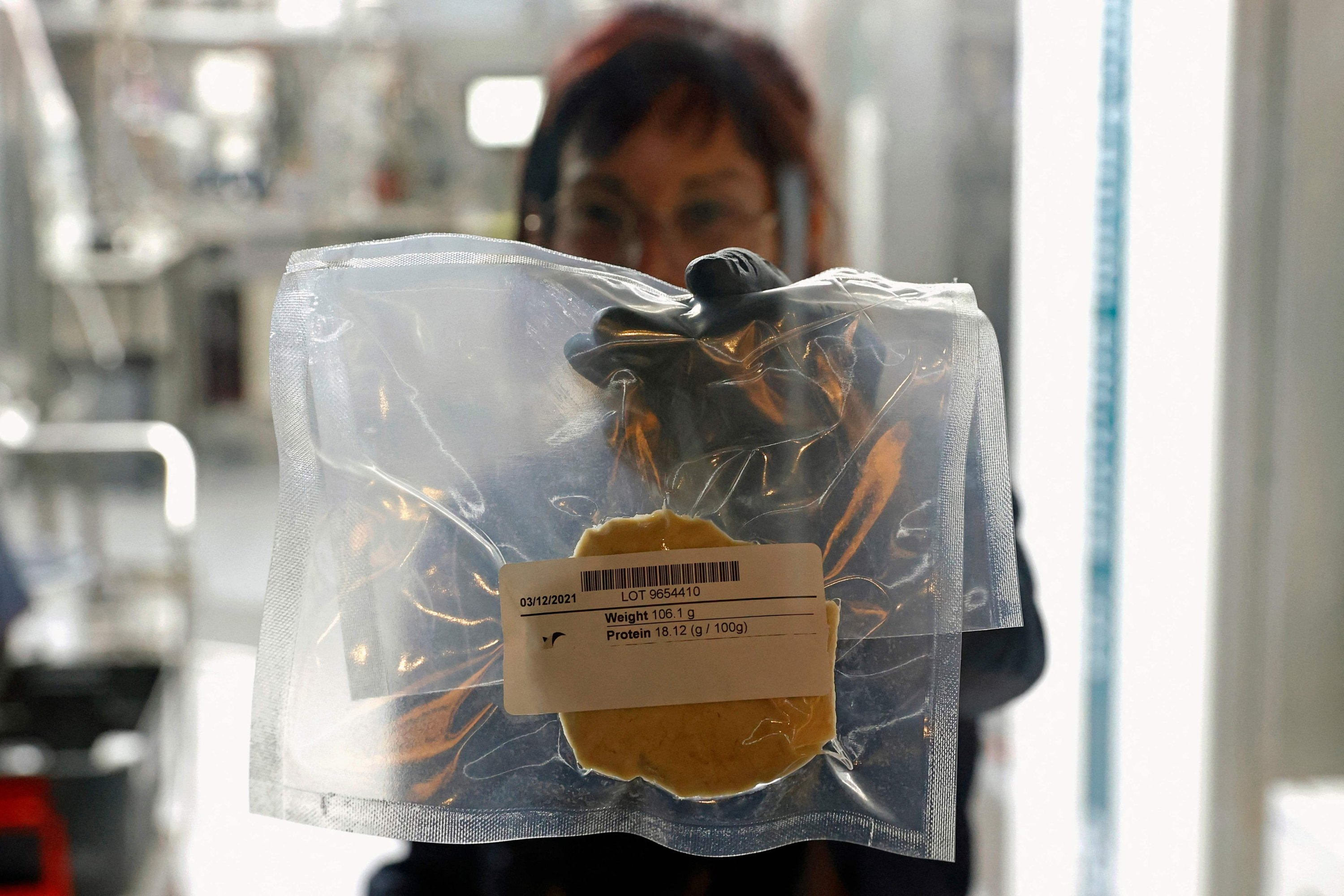 A technician displays lab-grown chicken meat in a sealed bag at the food-tech startup SuperMeat in Ness Ziona, central Israel, June 18, 2021. (AFP Photo)