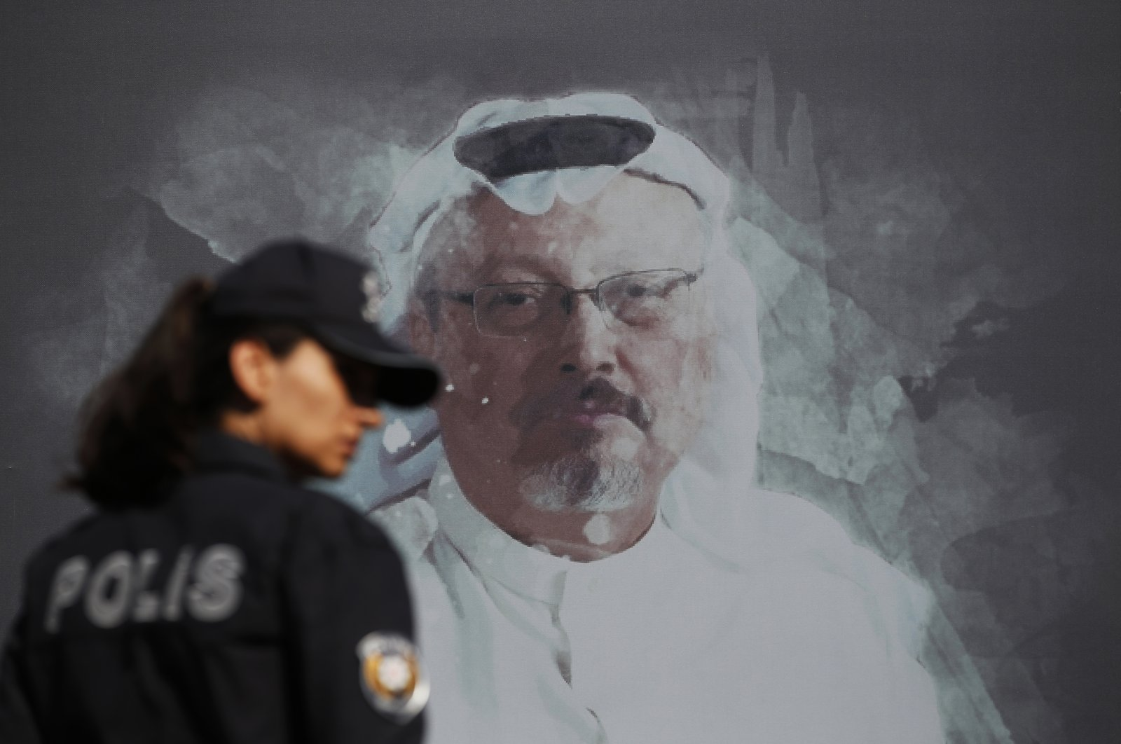 A Turkish police officer walks past a picture of slain Saudi journalist Jamal Khashoggi prior to a ceremony, near the Saudi Arabia consulate in Istanbul, marking the one-year anniversary of his death, Wednesday, Oct. 2, 2019. (AP File Photo)
