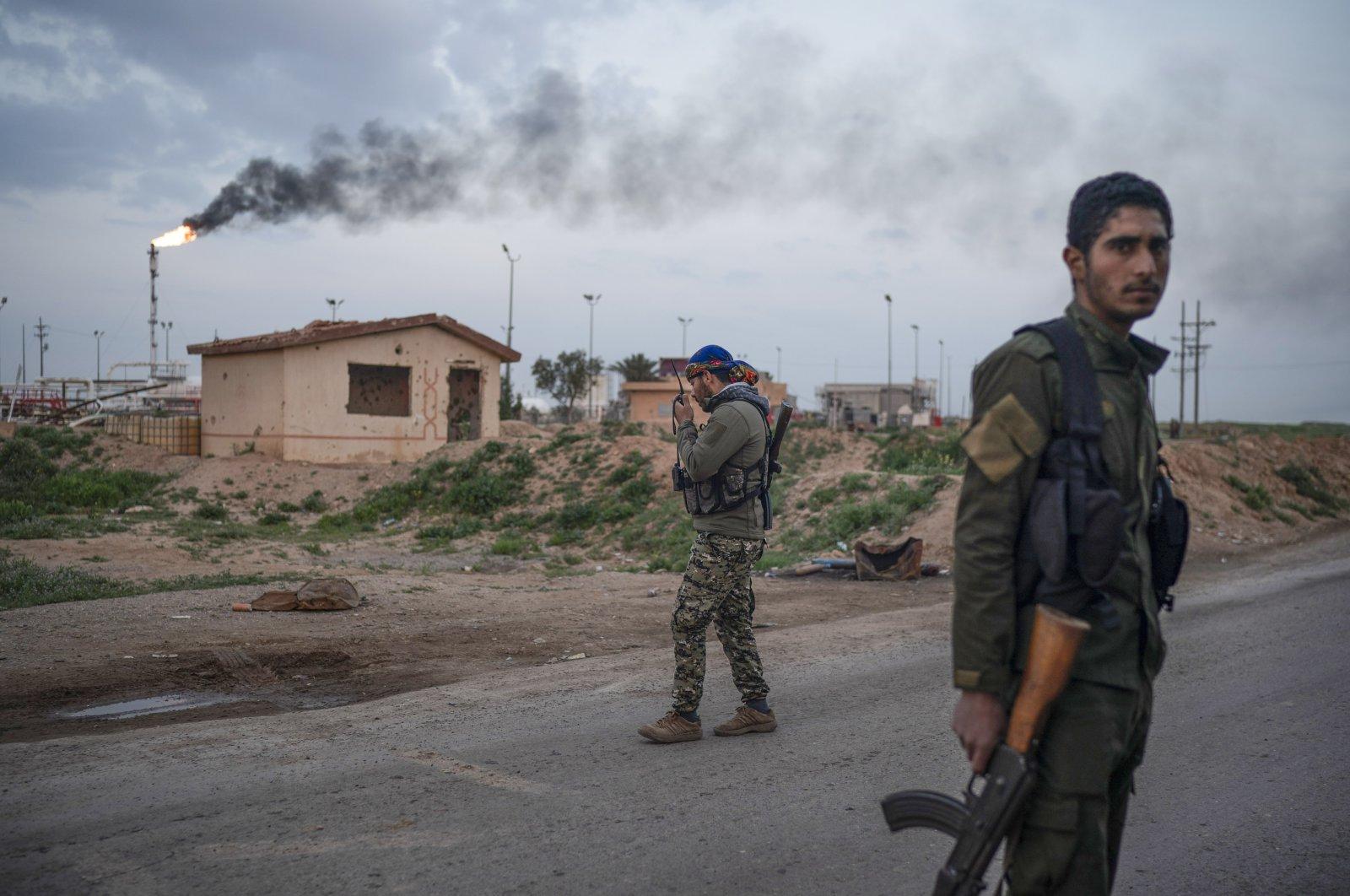 A YPG/PKK terrorist talks on his radio at a checkpoint near Omar oil field base, eastern Syria, Feb. 24, 2019. (AP File Photo)