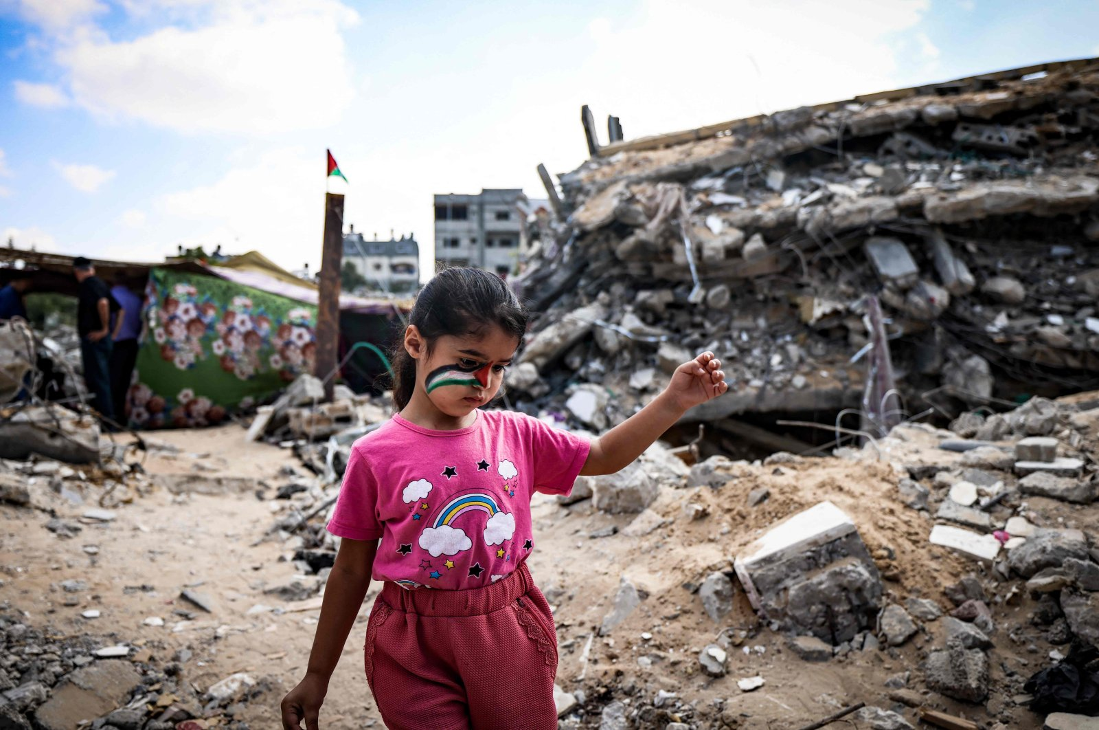 A Palestinian girl with a national flag painted on her face plays amidst the rubble of buildings destroyed by last month's Israeli bombardment of the Gaza Strip, in Beit Lahia, Palestine, June 19, 2021. (AFP Photo)