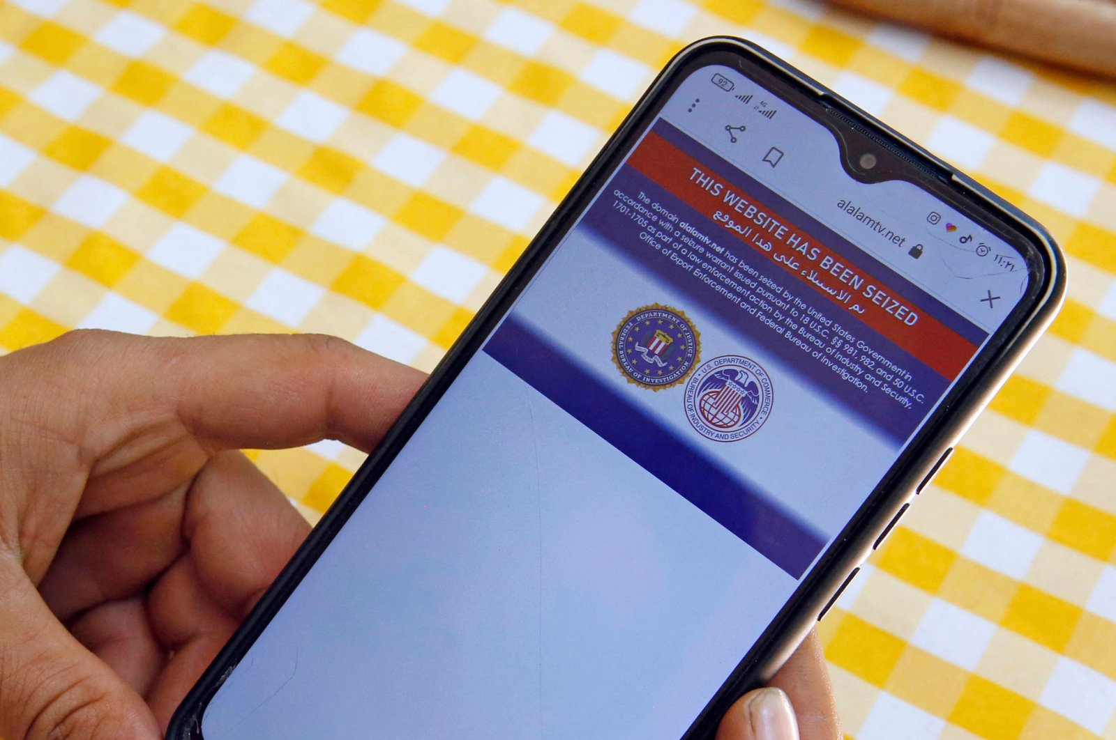 An Iranian man reads on his mobile phone a statement declaring Iran's Arabic-language channel Al-Alam's website 'has been seized' by the U.S. government, in Tehran, Iran, June 23, 2021. (AFP Photo)