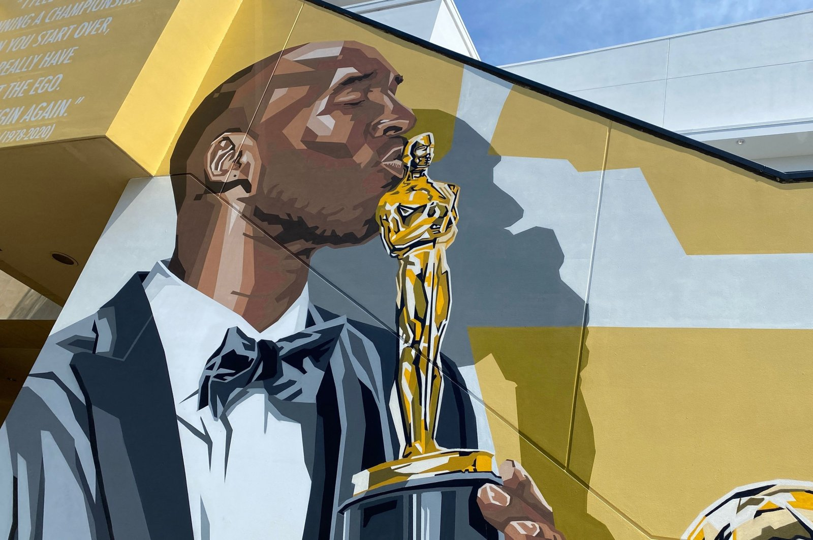 """A mural by artist Brian Peterson shows late LA Lakers icon Kobe Bryant holding his Oscar, won in 2018 for Best Animated Short Film """"Dear Basketball,"""" in the Dolby theater complex in Los Angeles, U.S., June 17, 2021. (AFP Photo)"""