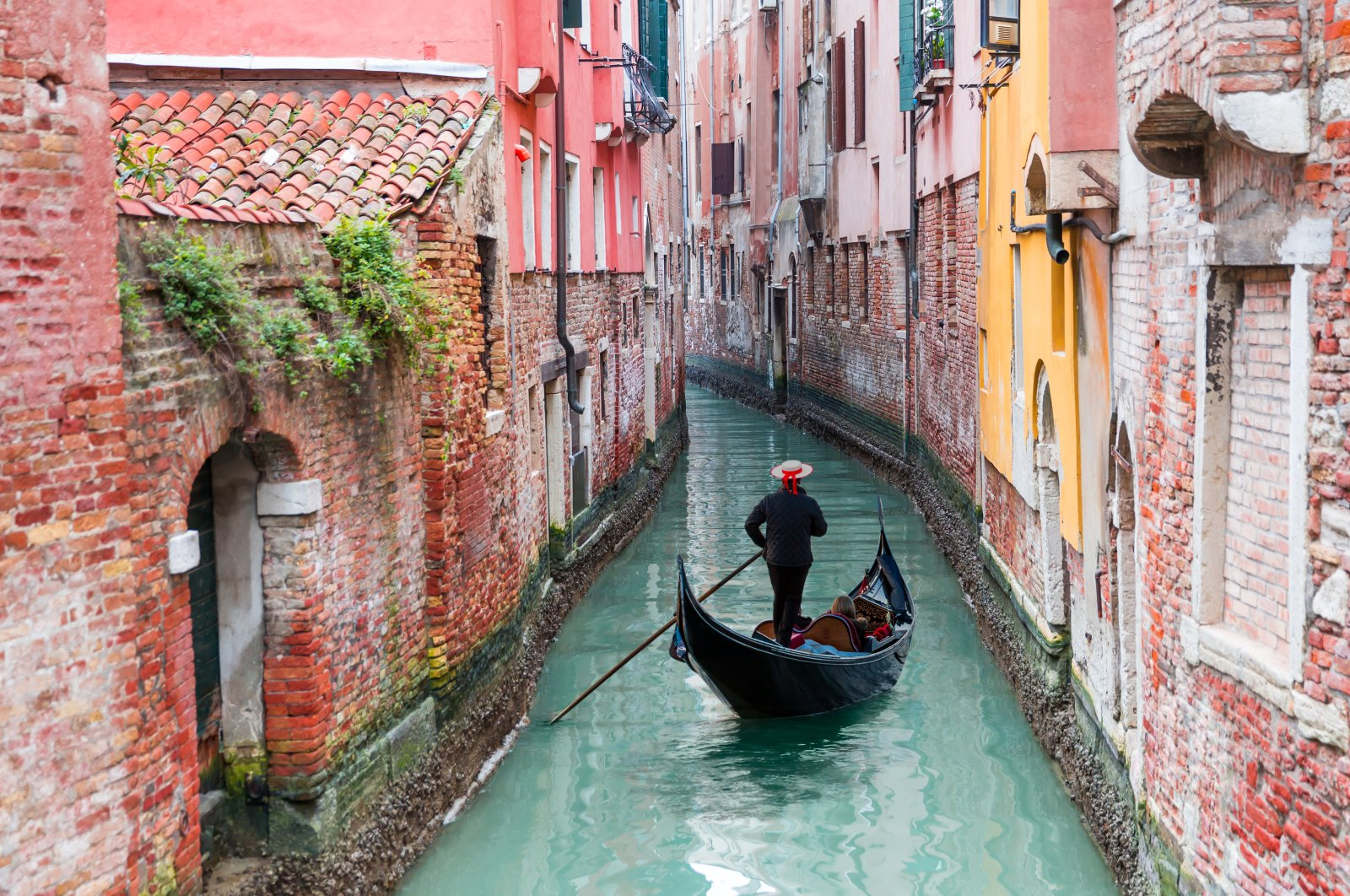 A Venetian gondolier punts a gondola through the green canal waters of Venice, Italy. (Shutterstock Photo)