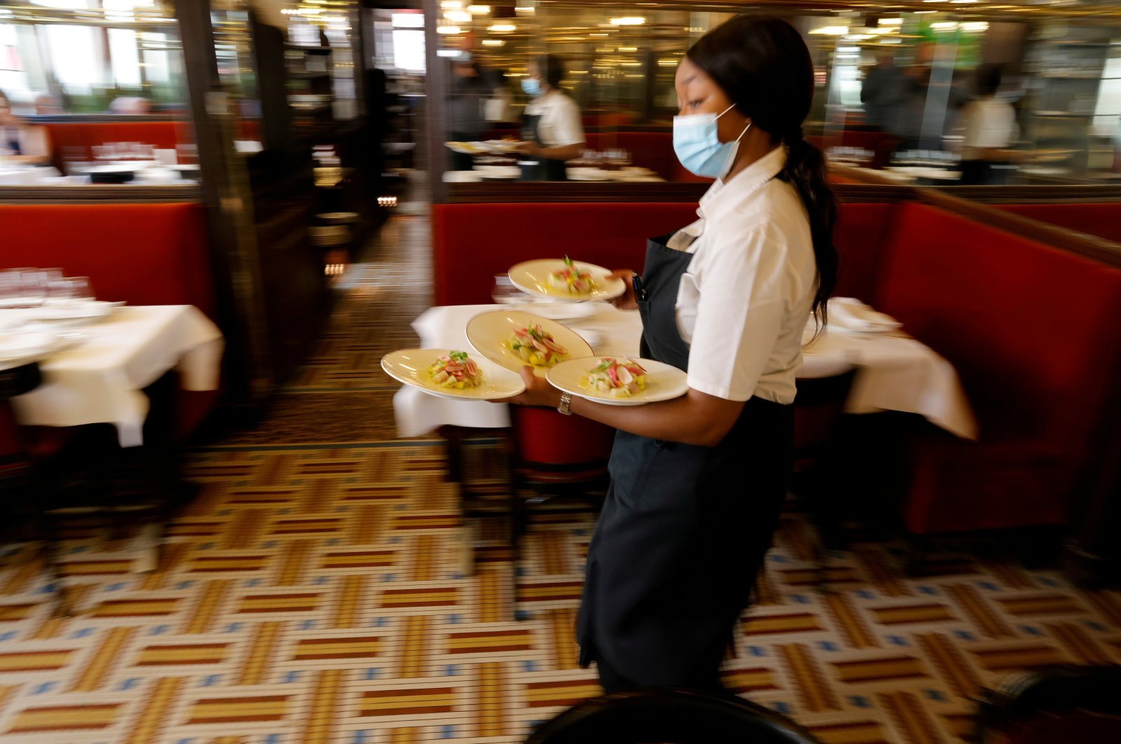 A waiter serves dishes in a restaurant as cafes and restaurants reopen indoor dining rooms in Paris, France, June 9, 2021. (Reuters Photo)