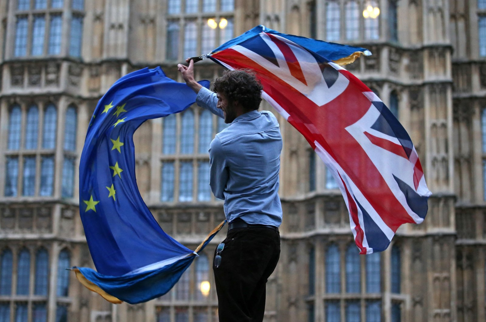 A man waves both a European Union flag and the U.K. flag together on College Green outside The Houses of Parliament at an anti-Brexit protest in central London, U.K., June 28, 2016. (AFP Photo)