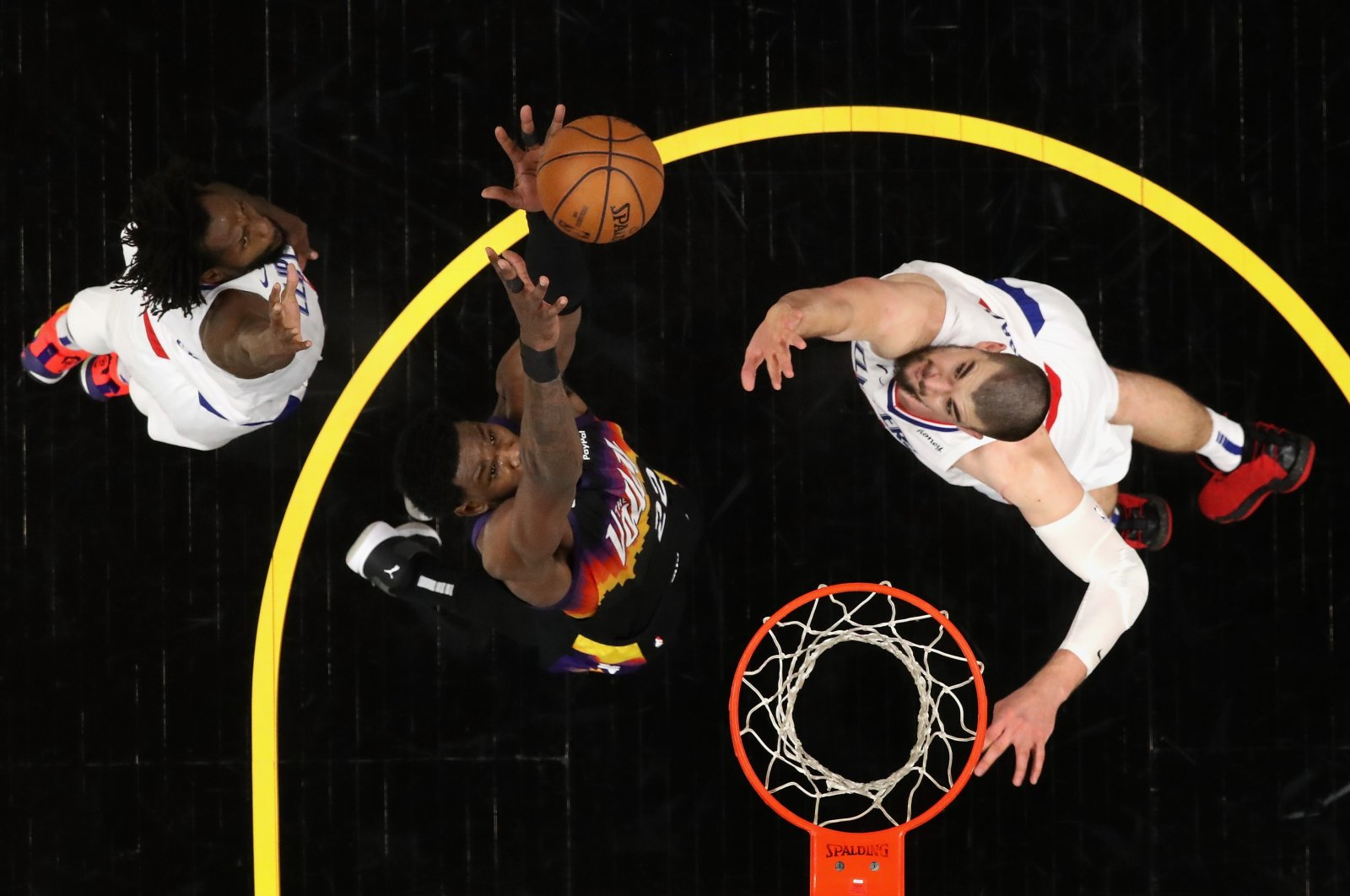 Phoenix Suns Deandre Ayton (C) catches the ball before a slam dunk over LA Clippers' Patrick Beverley (L) and Ivica Zubac during Game 2 of the Western Conference Finals at Phoenix Suns Arena, Phoenix, Arizona,  June 22, 2021. (AFP Photo)