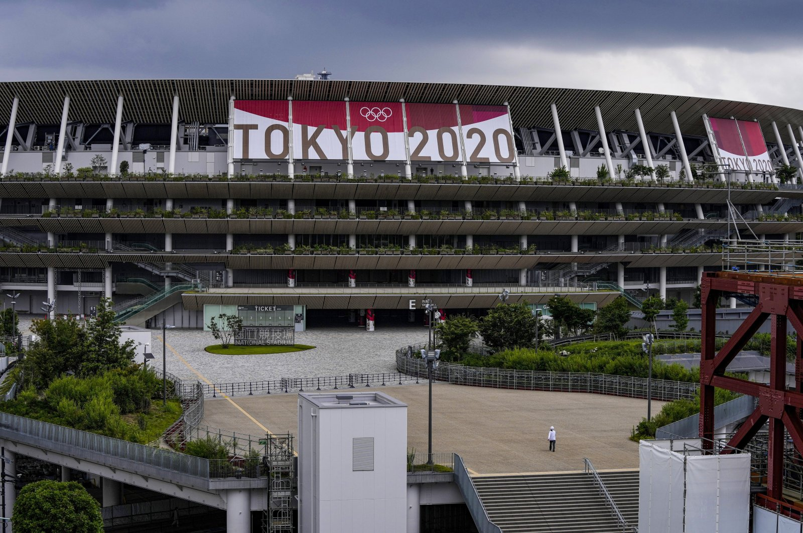 A worker walks through the front entrance of National Stadium, Tokyo, Japan, June 23, 2021. (AP Photo)