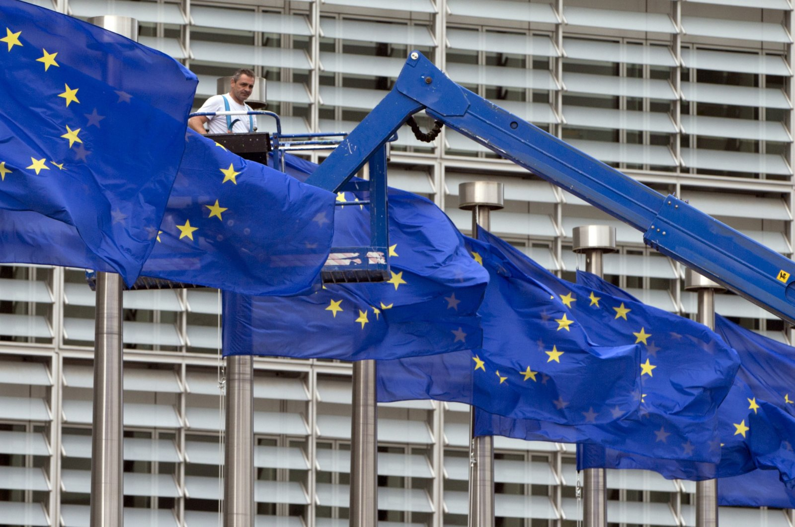 A worker on a lift adjusts the EU flags in front of EU headquarters in Brussels, Belgium, June 22, 2016. (AP File Photo)
