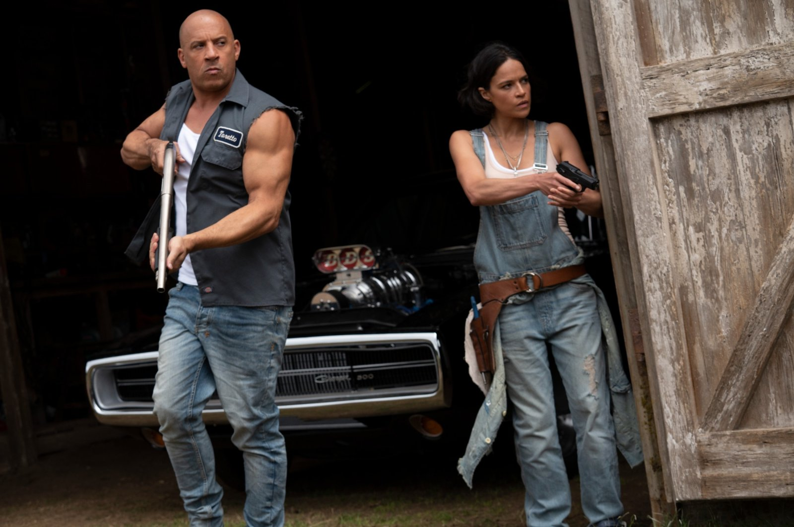 """Vin Diesel (L), and Michelle Rodriguez walk out of a barn holding weapons, in a scene from the movie""""F9: The Fast Saga."""" (Universal Pictures via AP)"""