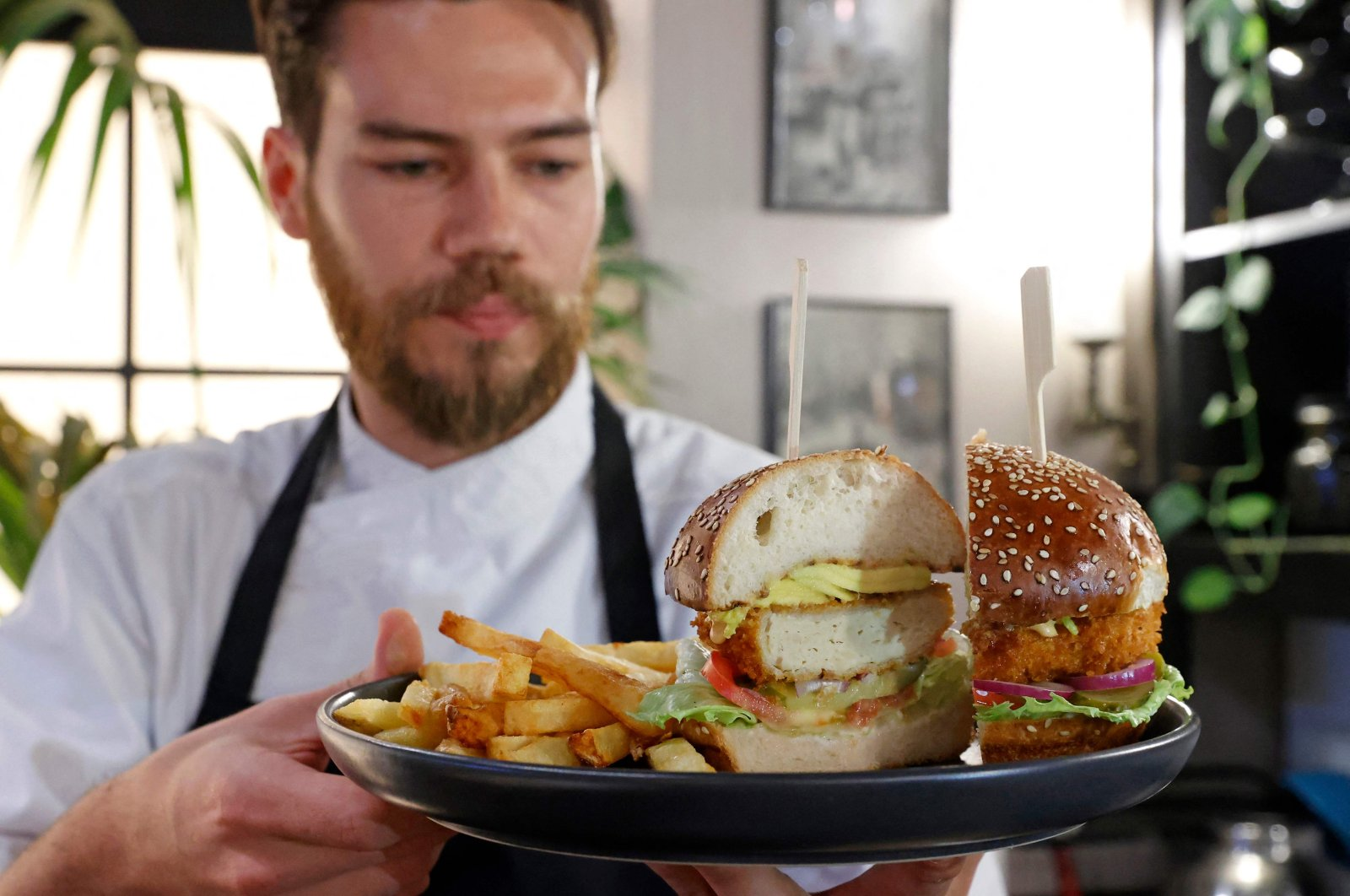 """Israeli Chef Shachar Yogev serves a burger made with """"cultured chicken"""" meat at a restaurant adjacent to the SuperMeat production site in Ness Ziona, central Israel, June 18, 2021. (AFP Photo)"""