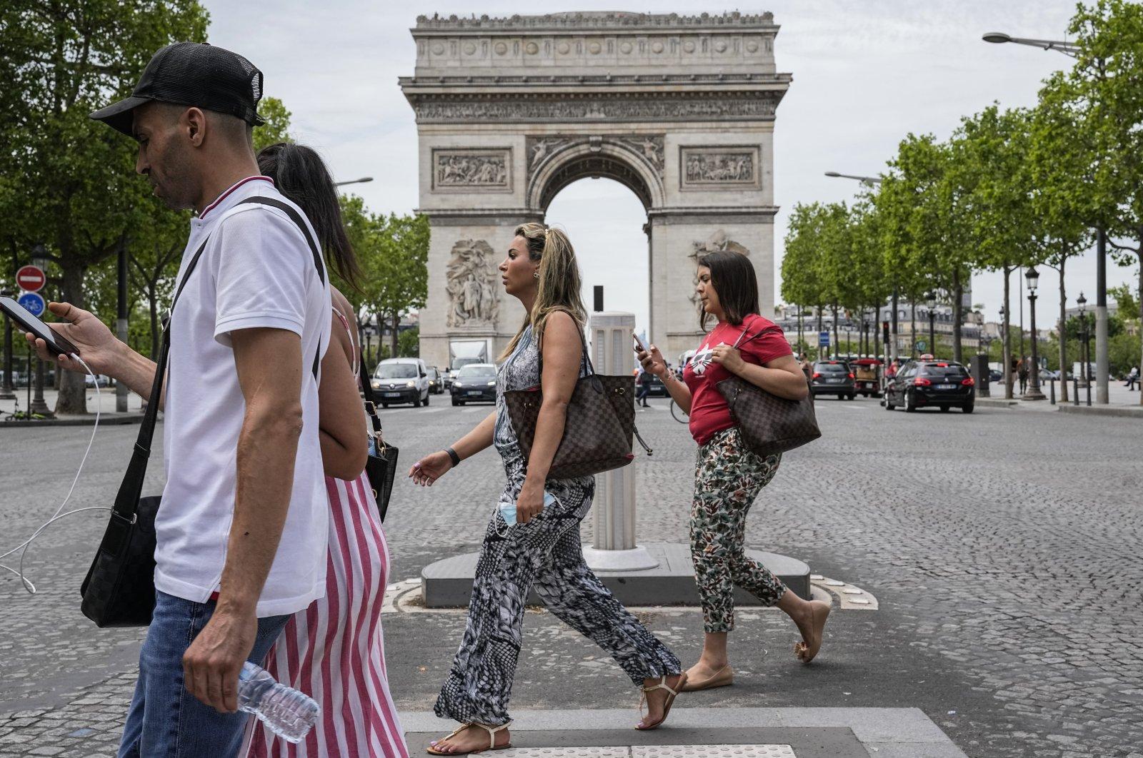 People cross Champs Elysees avenue in Paris, France, June 17, 2021. (AP Photo)