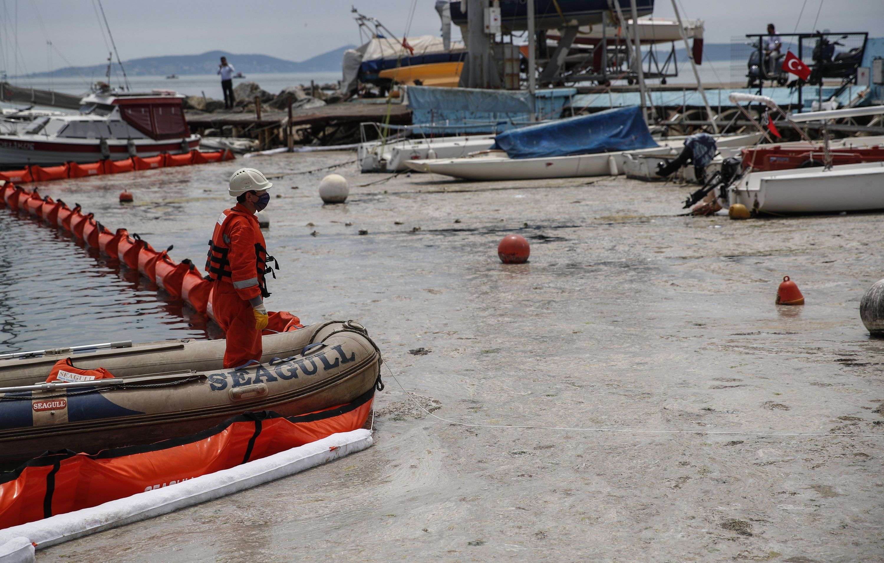 Experts work to clear a mass of marine mucilage from Marmara Sea at the Caddebostan shore, in Asian side of Istanbul, Turkey, June 8, 2021. (AP Photo)