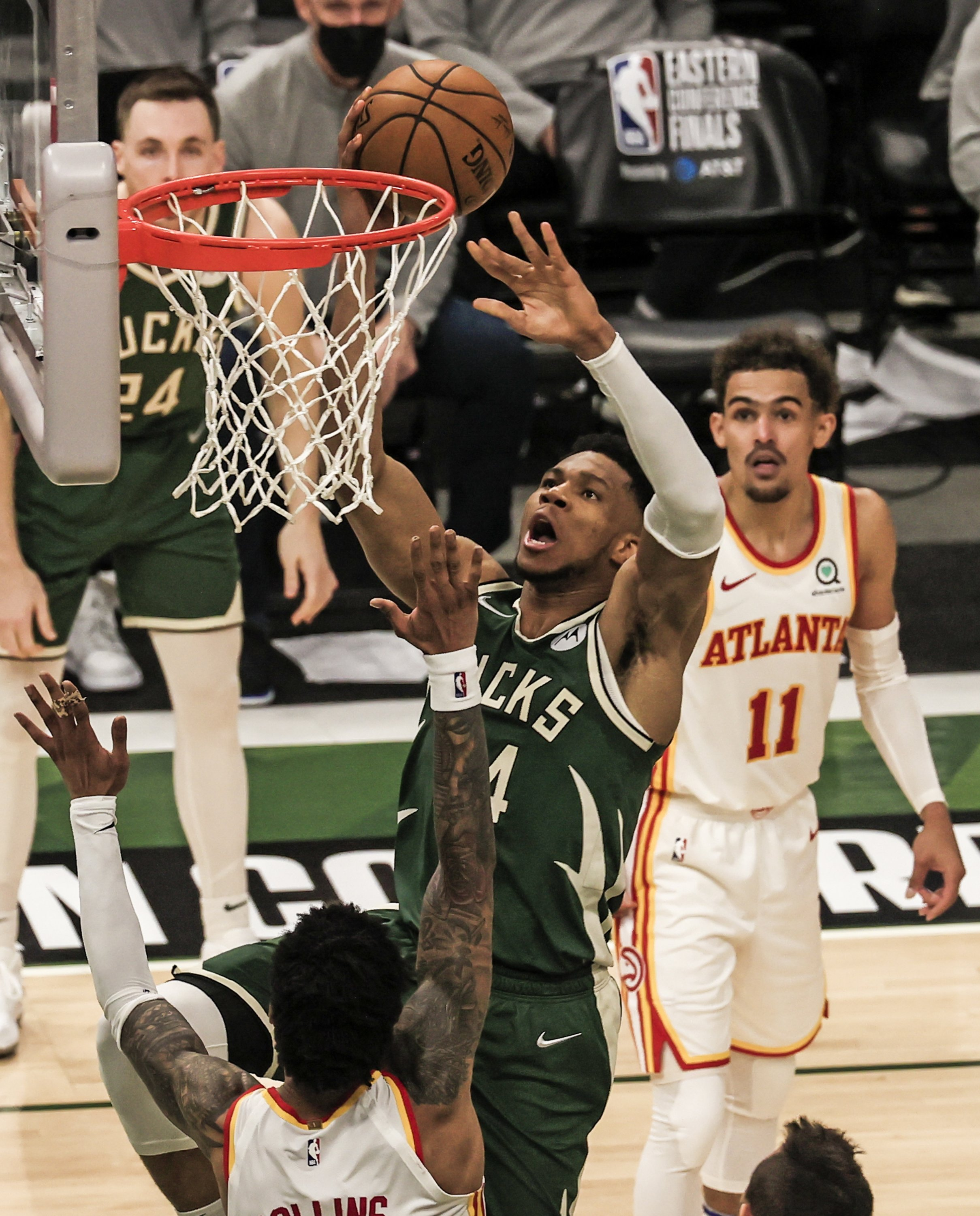 Atlanta Hawks guard Trae Young (R) watches as Milwaukee Bucks forward Giannis Antetokounmpo (C) shoots on Hawks forward John Collins (L) during Game 1 of the Eastern Conference Finals for the 2021 NBA Playoffs at Fiserv Forum, Milwaukee, Wisconsin, U.S., June 23, 2021. (EPA Photo)