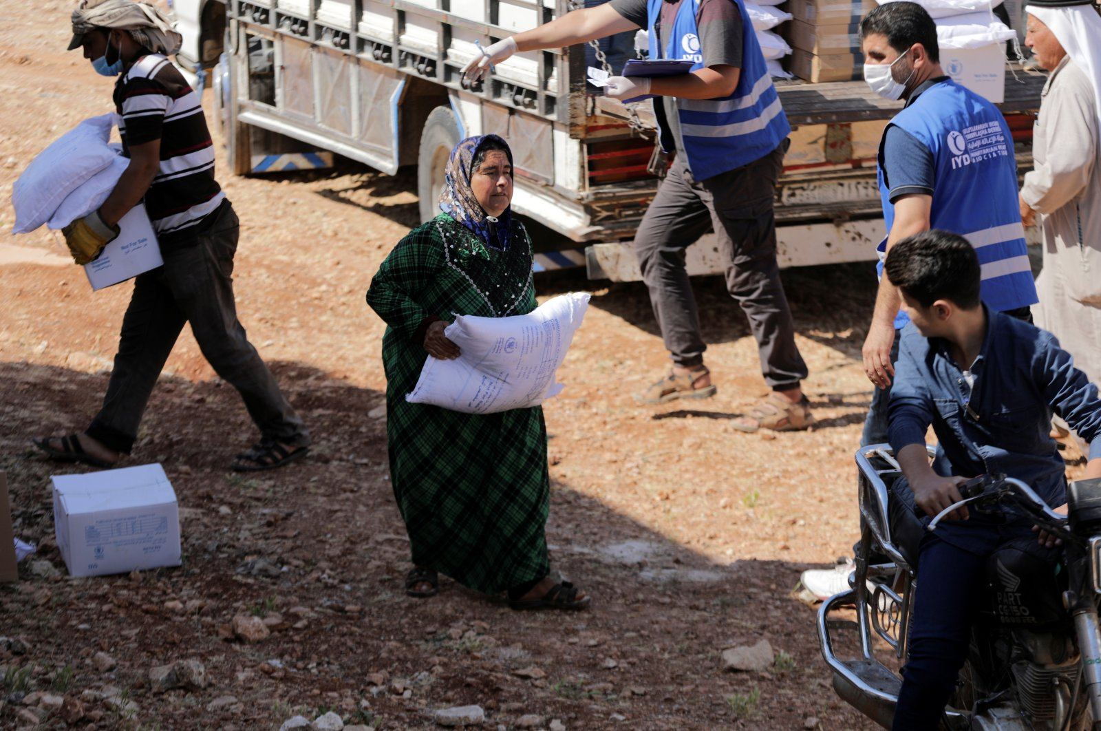An internally displaced Syrian woman walks as she holds a bag of humanitarian aid in the opposition-held Idlib, Syria, June 9, 2021. (Reuters Photo)