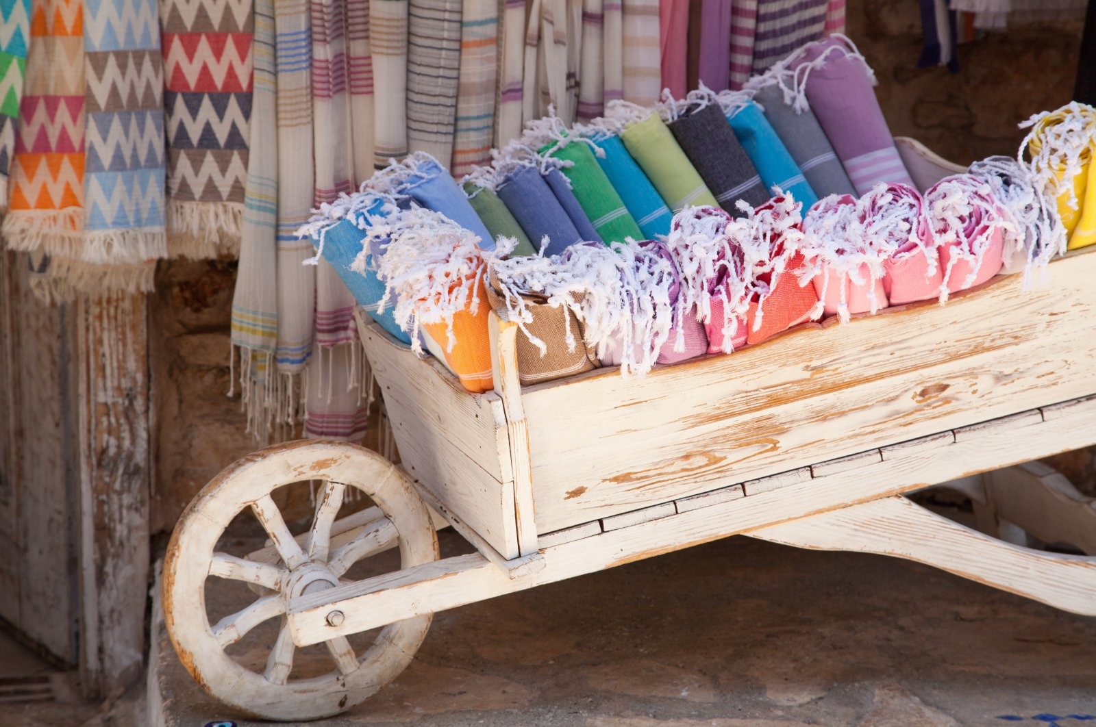 Multicolored Turkish bath towels in a wooden cart. (Shutterstock Photo)