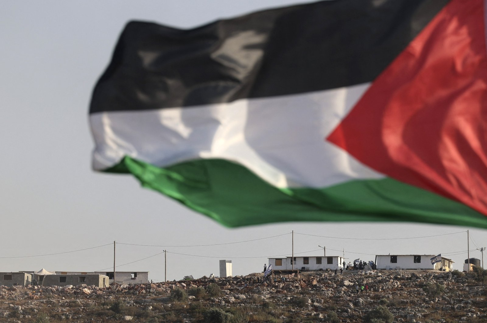 A Palestinian flag flutters across the valley from the newly built Israeli settlers' outpost of Eviatar, near the village of Beita, south of Nablus, in the occupied West Bank, Palestine, June 13, 2021. (AFP Photo)