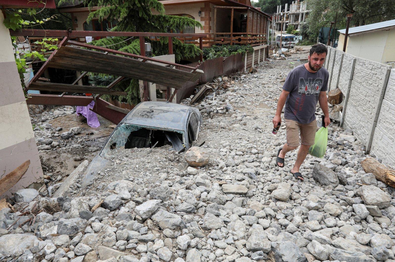 A man walks along a damaged street after heavy rainfall and floods in Yalta, Crimea, June 22, 2021. (Reuters Photo)