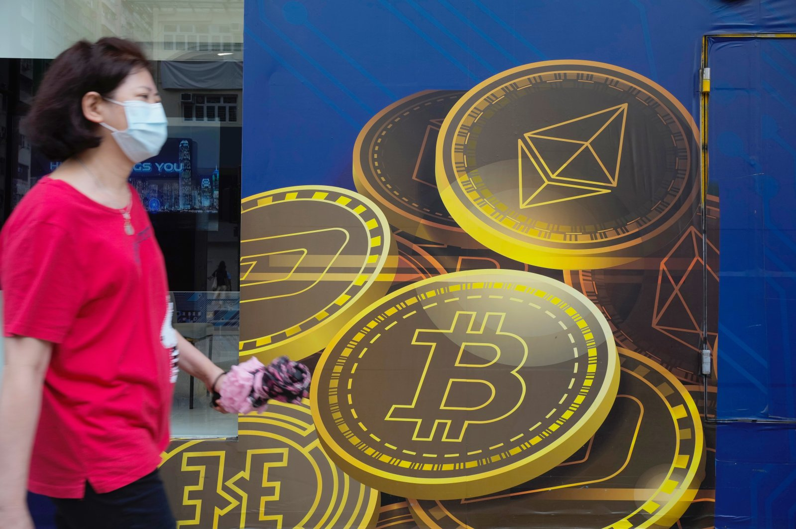 In this June 1, 2021, file photo, a woman walks past an advertisement for Bitcoin in Hong Kong. (AP Photo)