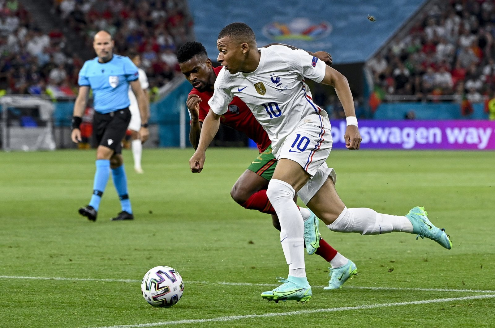 France's Kylian Mbappe (R) is challenged by Portugal's Nelson Semedo (L) for the ball during their Euro 2020 Group F match at Puskas Arena in Budapest, Hungary, June 23, 2021. (EPA Photo)