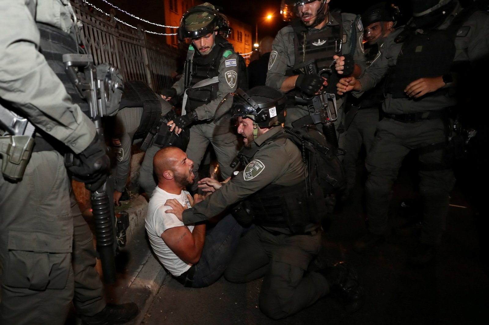 A Palestinian protester is detained during clashes with Israeli police, as the Muslim holy fasting month of Ramadan continues, in Jerusalem, April 23, 2021. (Reuters Photo)