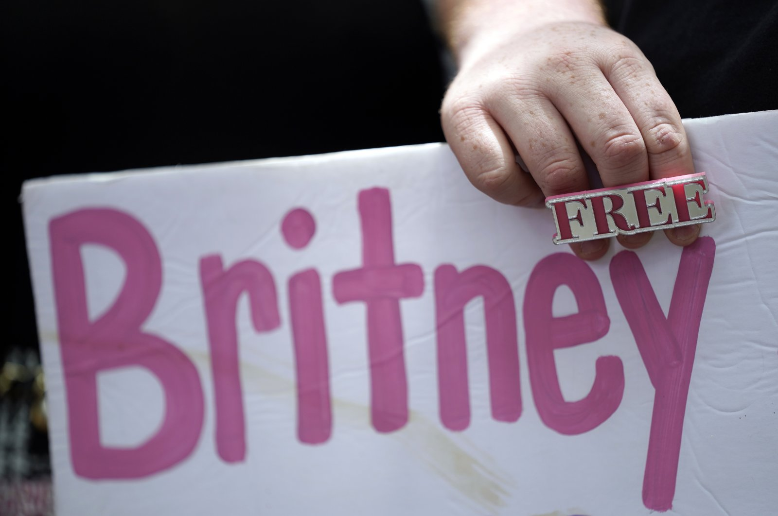 A Britney Spears supporter holds a sign outside a court hearing concerning the pop singer's conservatorship at the Stanley Mosk Courthouse in Los Angeles, U.S., June 23, 2021. (AP Photo)
