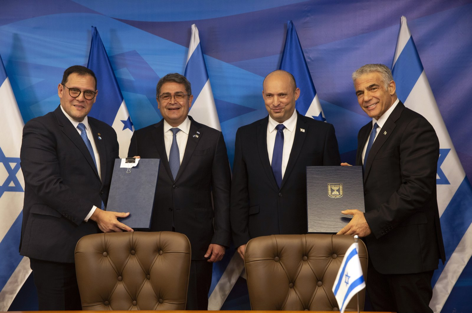 Israeli Prime Minister Naftali Bennett (2nd R), and Honduran President Juan Orlando Hernandez (2nd L), look on as Israeli Foreign Minister Yair Lapid (R), and Honduran Foreign Minister Lisandro Rosales hold signed agreements between their two countries at the prime minister's office, Jerusalem, June 24, 2021. (AP Photo)