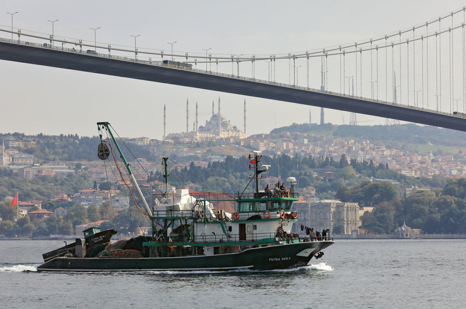 A fishing vessel sails under Bosphorus Bridge along the Bosphorus Strait, Istanbul, Turkey, Oct. 6, 2020. (Shutterstock Photo)