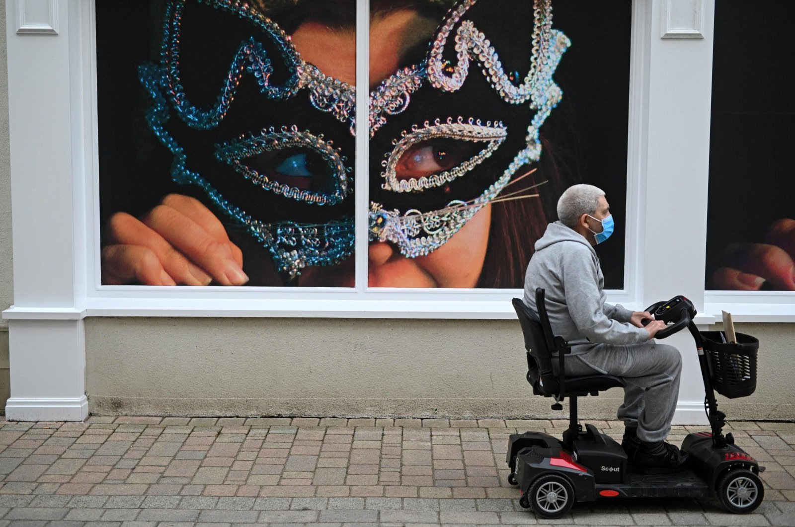 A man wearing a mask due to COVID-19 rides a mobility scooter past posters advertising the town's Winter Droving festival in Penrith, Cumbria, northwest England, on June 21, 2021. (AFP Photo)