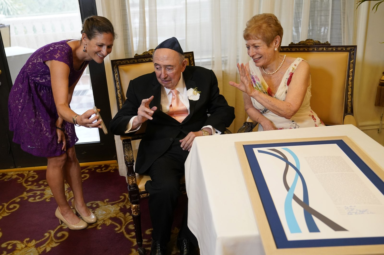 A couple waveto family members on a cell phone after signing the ketubah, a Jewish marriage contract, before their wedding ceremony at The Palace Coral Gables, a senior living residence, in Coral Gables, Florida, U.S.,June 22, 2021. (AP Photo)
