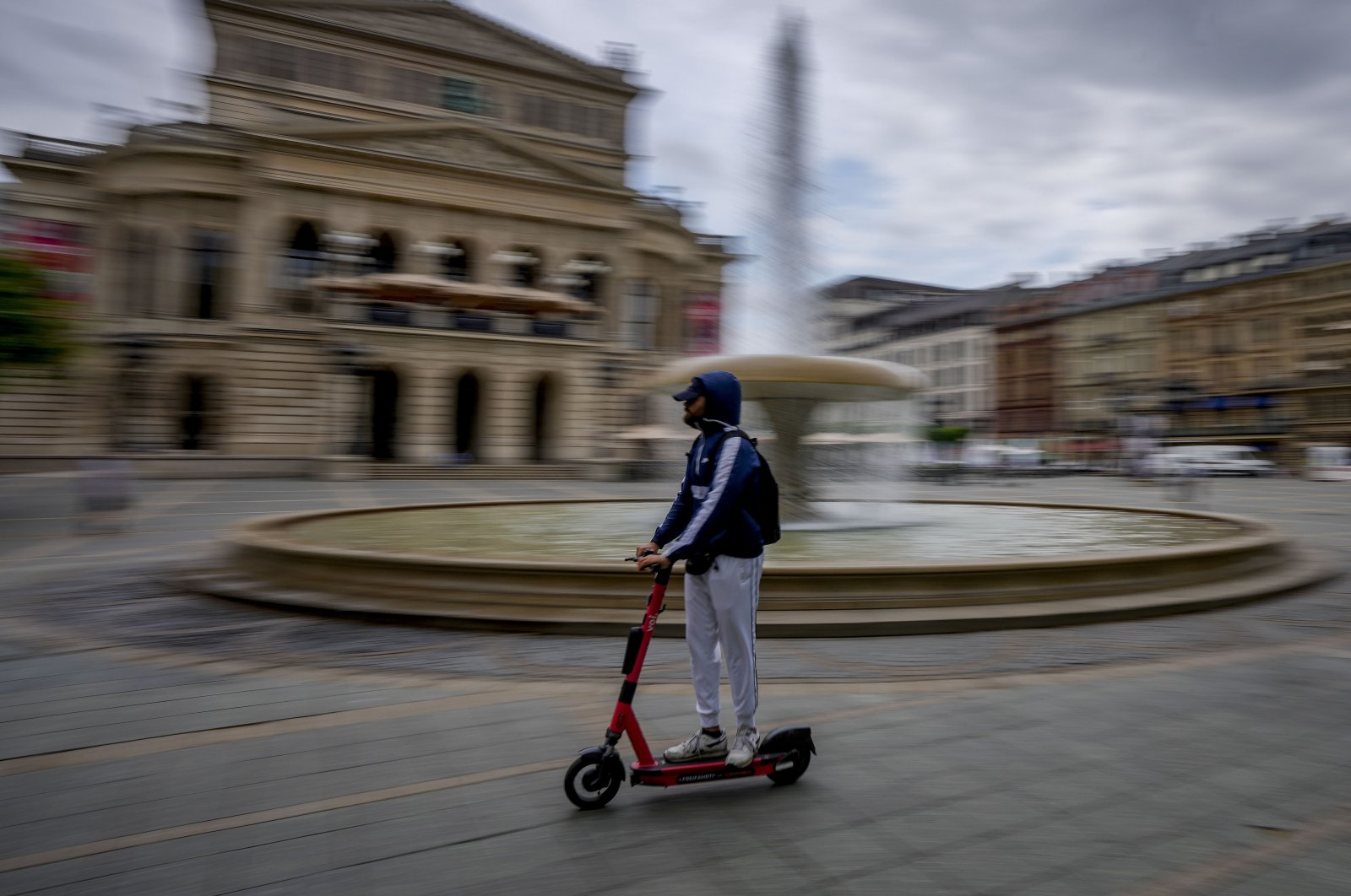 A man riding an e-scooter passes in front of the Old Opera in Frankfurt, Germany, June 22, 2021. (AP Photo)