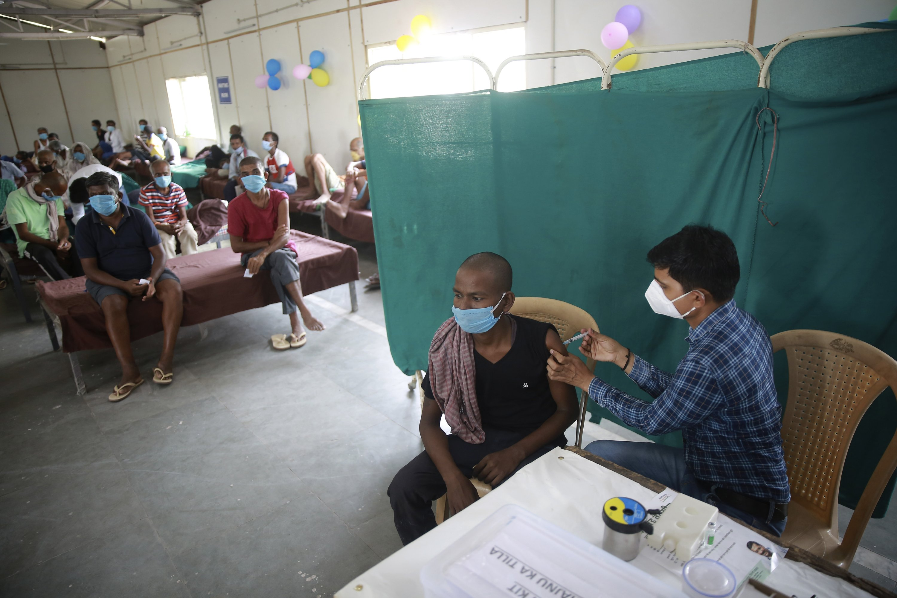 A health worker administers a COVID-19 vaccine during a vaccination drive aimed at the homeless in New Delhi, India, June 25, 2021. (AP Photo)