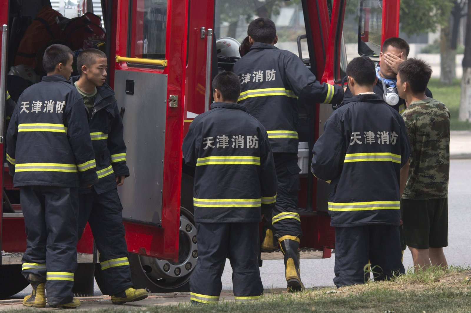 Chinese firefighters wait near the site of an explosion in northeastern China's Tianjin municipality, Aug. 15, 2015. (AP Photo)
