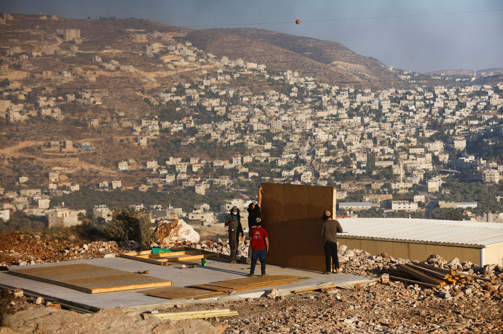 Jewish settlers construct a structure in a new Israeli settler outpost near the Palestinian village of Beita, in Givat Eviatar, Israeli-occupied West Bank, Palestine, June 23, 2021. (Reuters Photo)