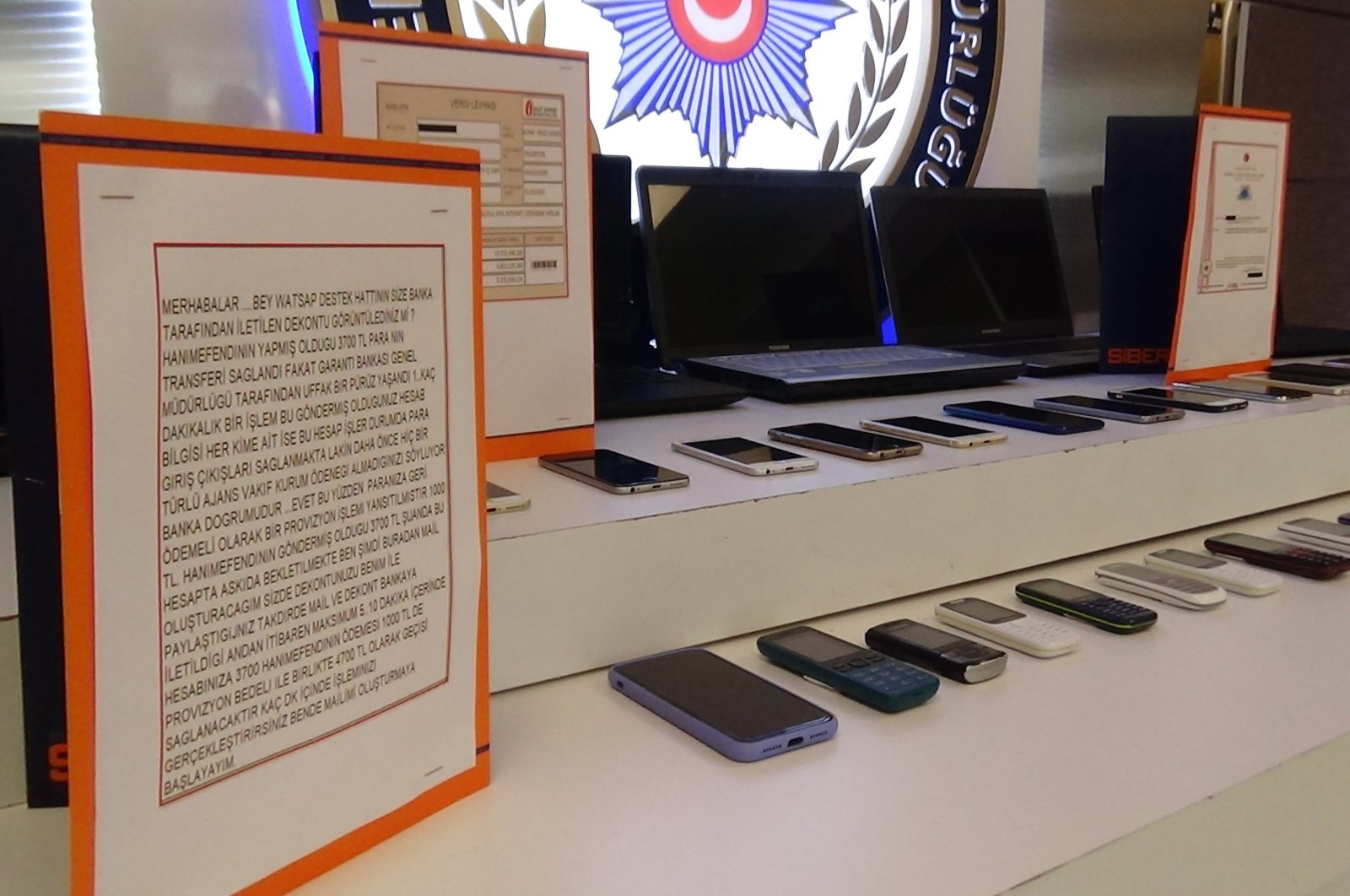Police display cellphones, computers and transcripts of exchanges between suspected gang members and victims, Istanbul, Turkey, June 25, 2021. (İHA PHOTO)
