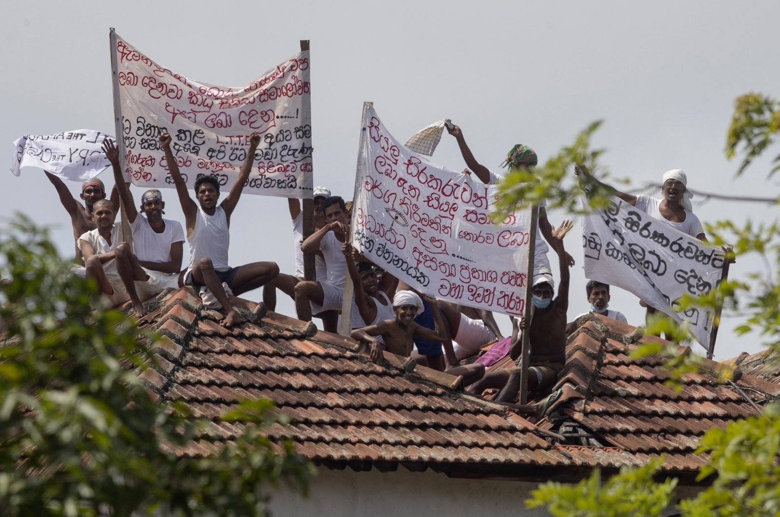 Death-row inmates of Sri Lanka's Welikada prison protest holding banners from the roof of the prison in Colombo, Sri Lanka, Friday, June 25, 2021. (AP Photo)