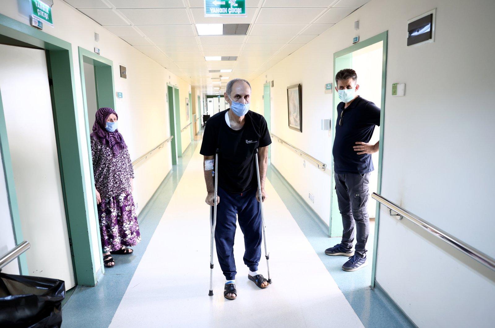 Vakkas Orhan (C) walks on crutches at the hospital, in the capital Ankara, Turkey, June 25, 2021. (AA Photo)