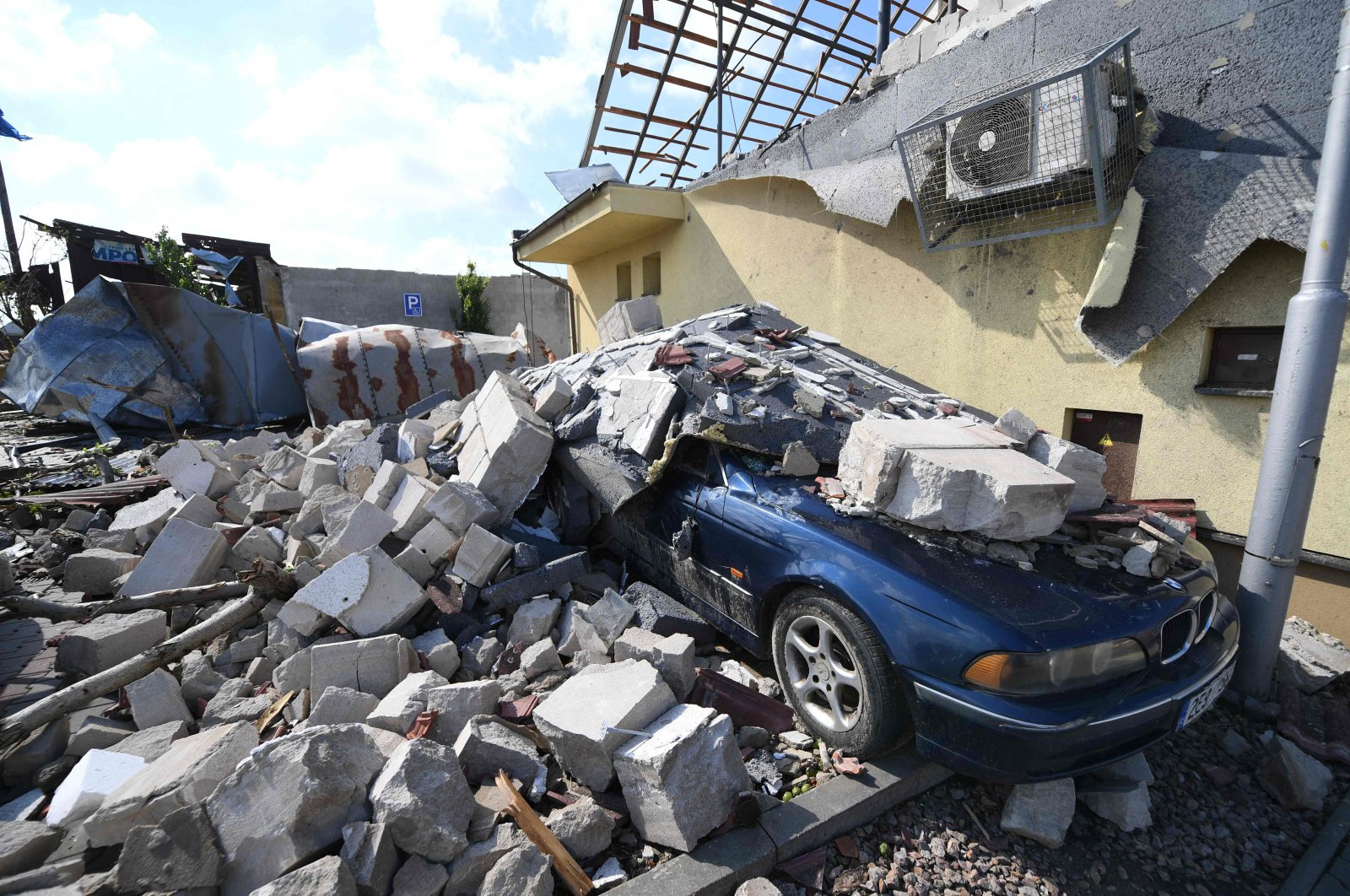 A car is consumed by the rubble of damaged houses after they were hit by a tornado, in the village of Moravska Nova Ves, some 60 kilometers (37 miles) south of Brno, South Moravia, Czech Republic, on June 25, 2021. (AFP Photo)