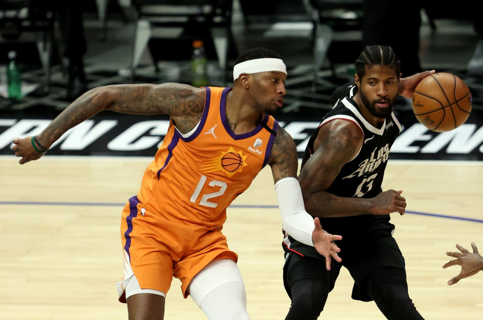 LA Clippers' Paul George (R) tries to keep possession againstPhoenix Suns' Torrey Craig during Game 3 of the Western Conference Finals at Staples Center, Los Angeles, California, U.S., June 24, 2021. (AFP Photo)