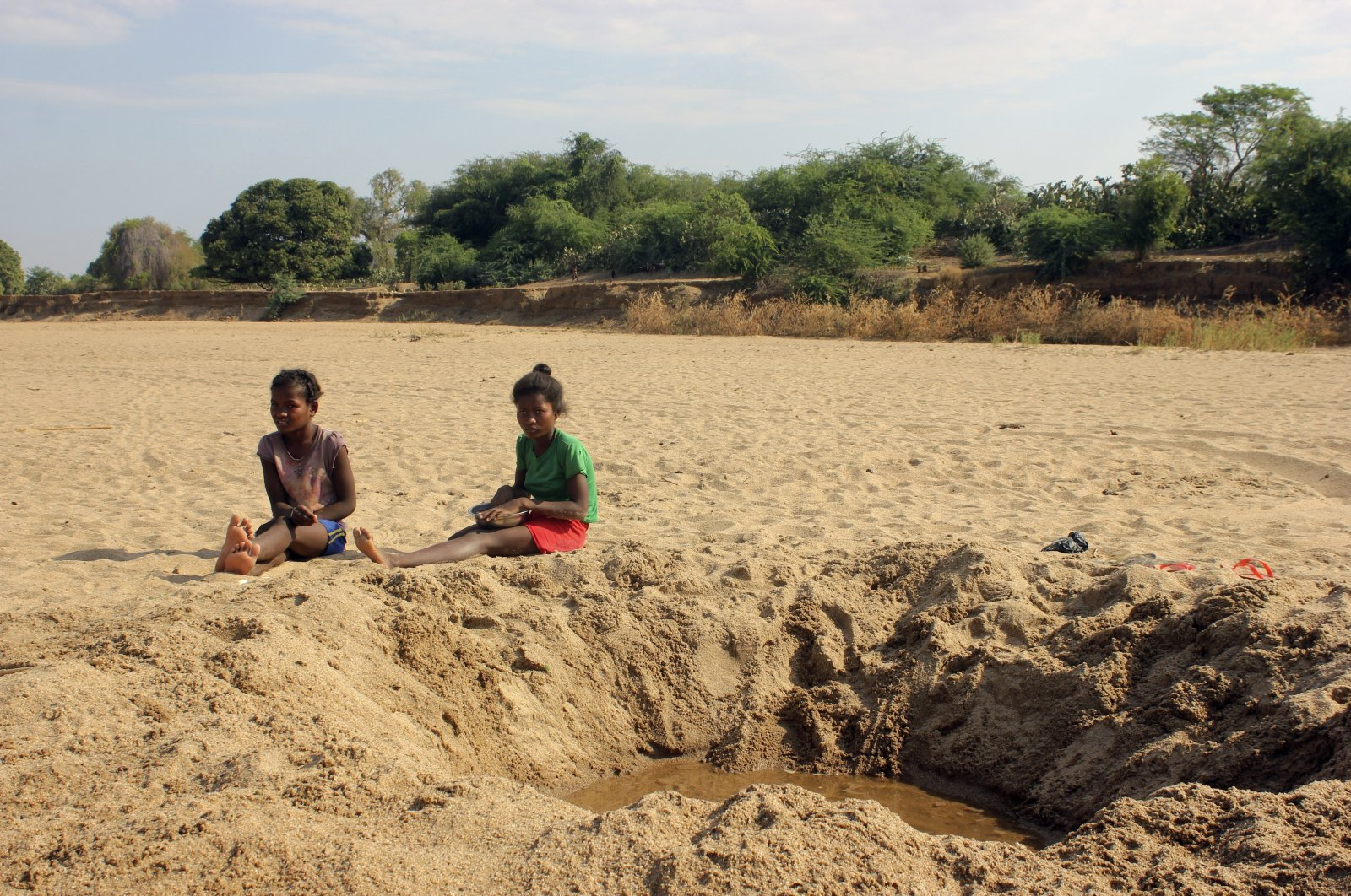 Children sit by a dug out water hole in a dry river bed in the remote village of Fenoaivo, Madagascar, Nov. 11, 2020. (AP Photo)